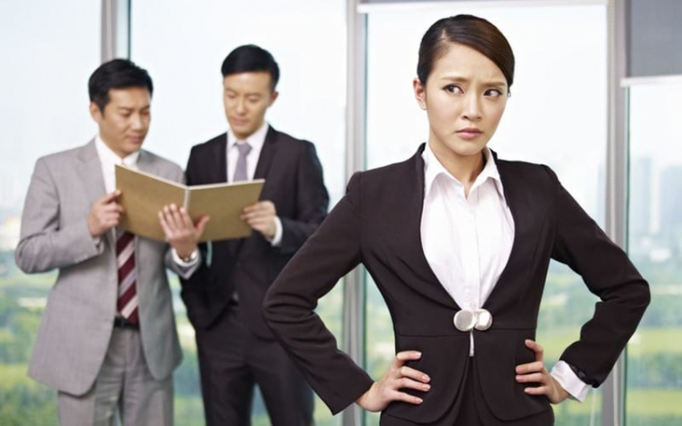 17974998 - portrait of a young asian businesswoman with her colleagues in the background